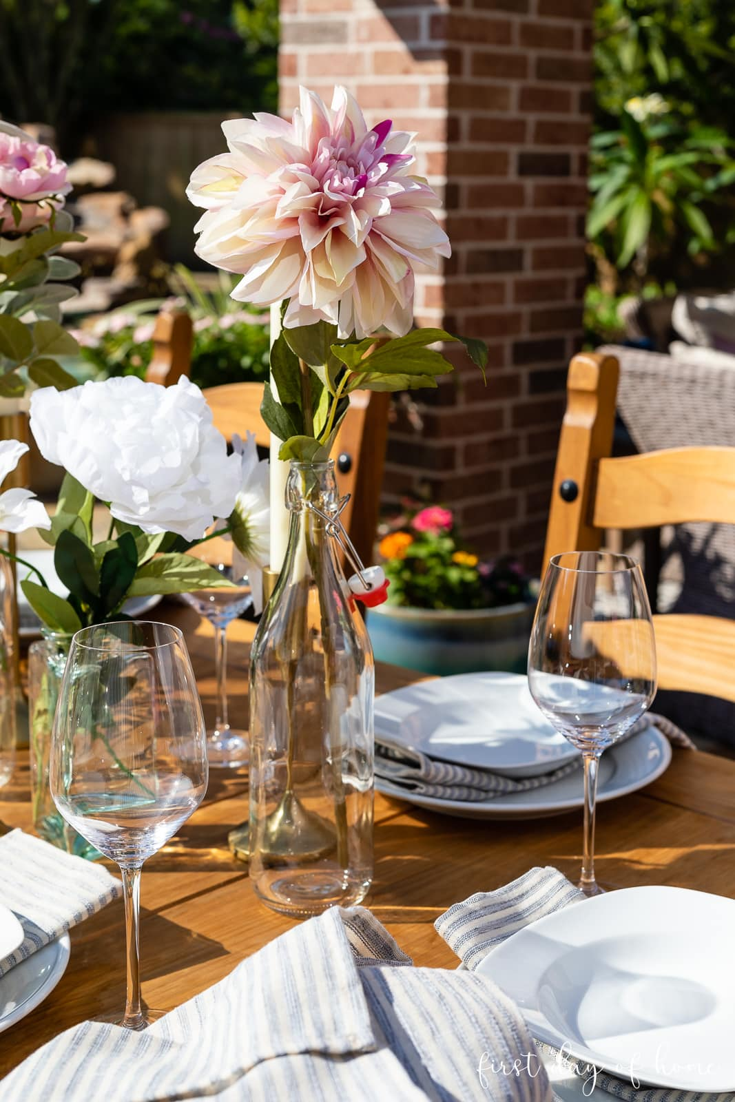Dahlia in glass bottle on summer outdoor dining table