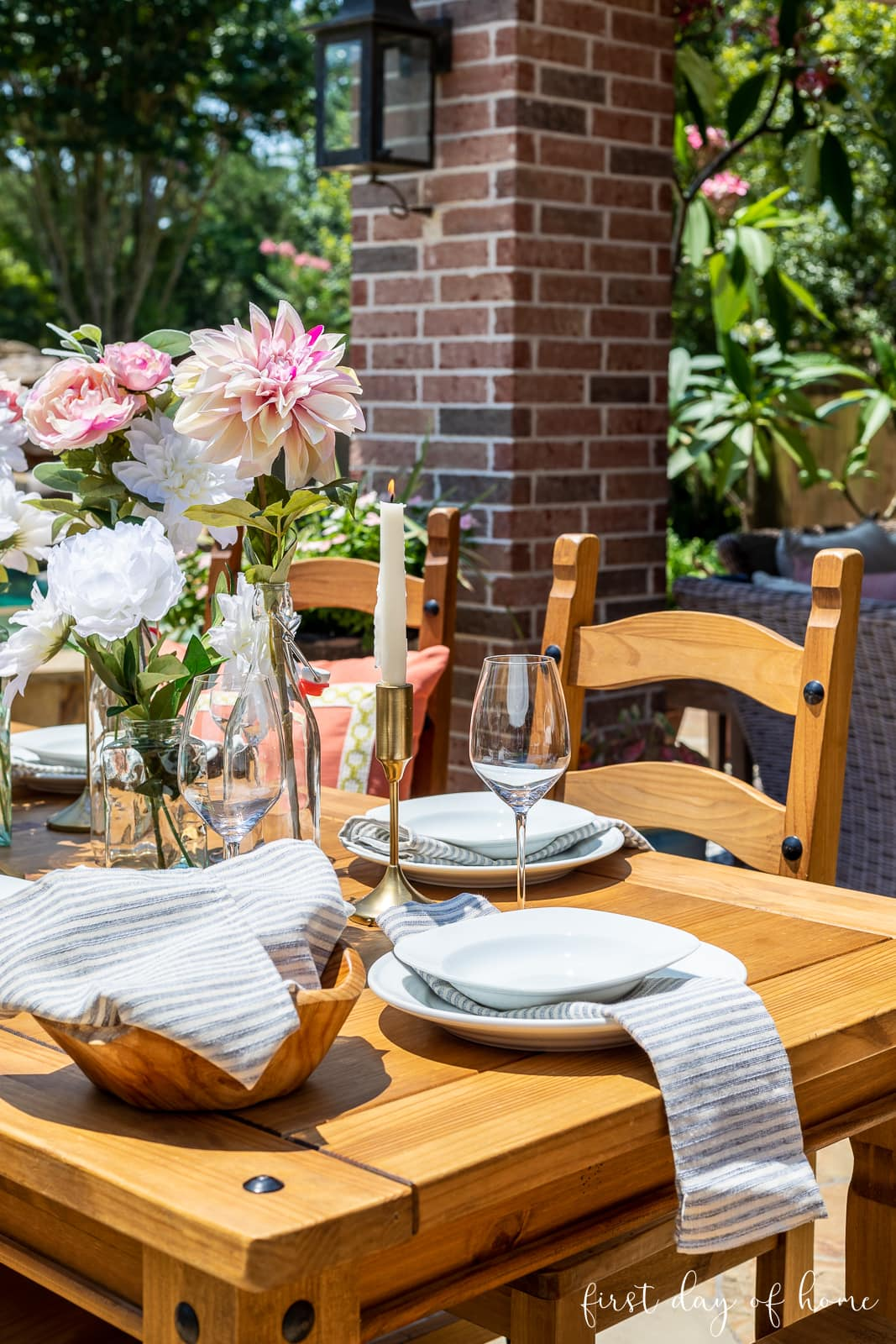 Outdoor table decorations with taper candles, faux florals and glass bottles