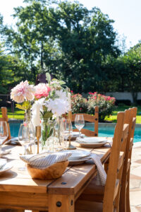 Outdoor dining table decorations with floral centerpiece and taper candles
