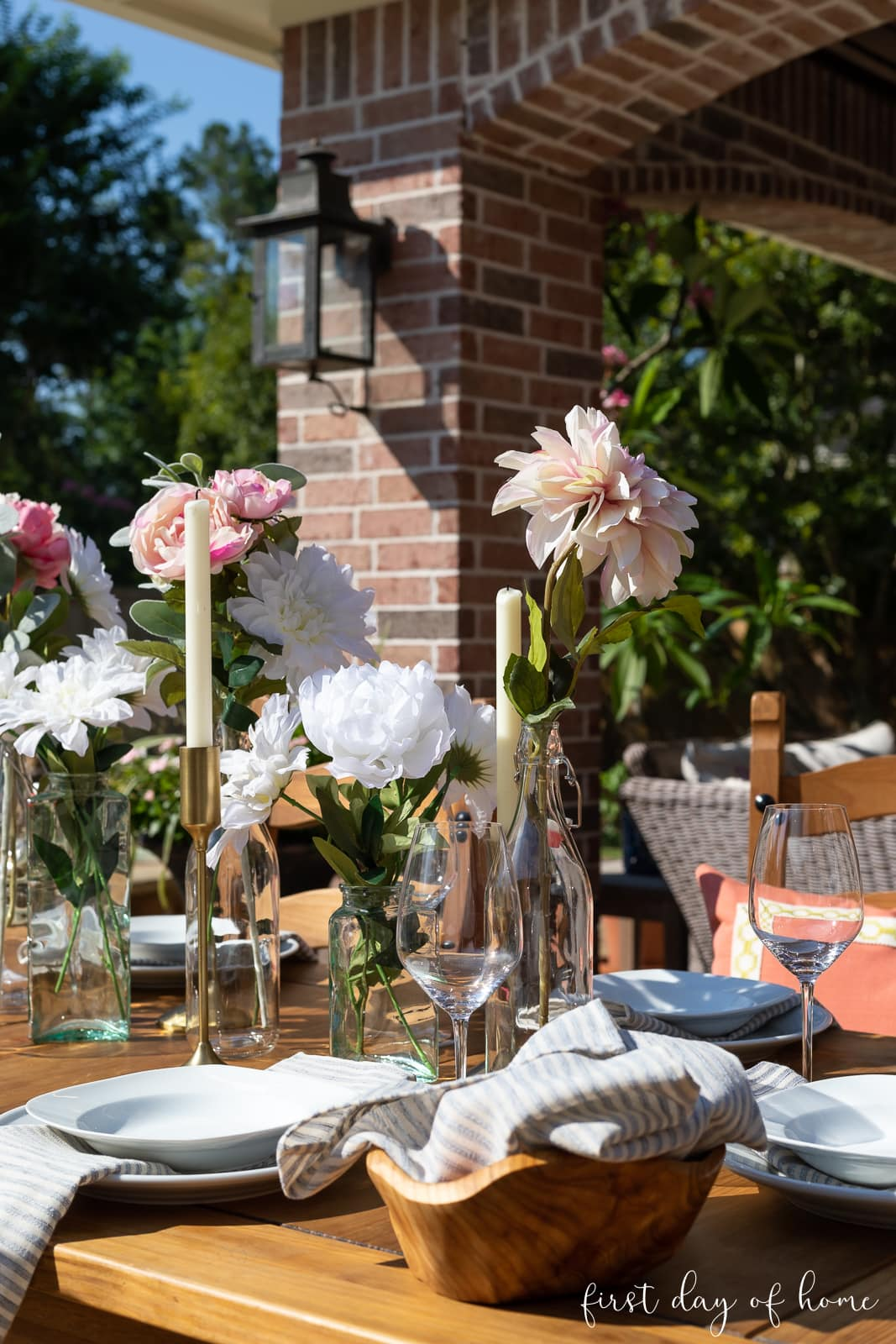 Outdoor dining table with floral centerpieces and neutral place settings