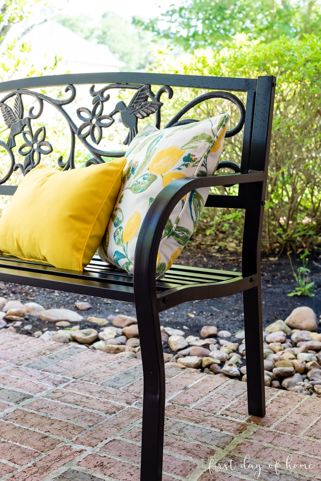 Black bench with lemon patterned and yellow outdoor throw pillows