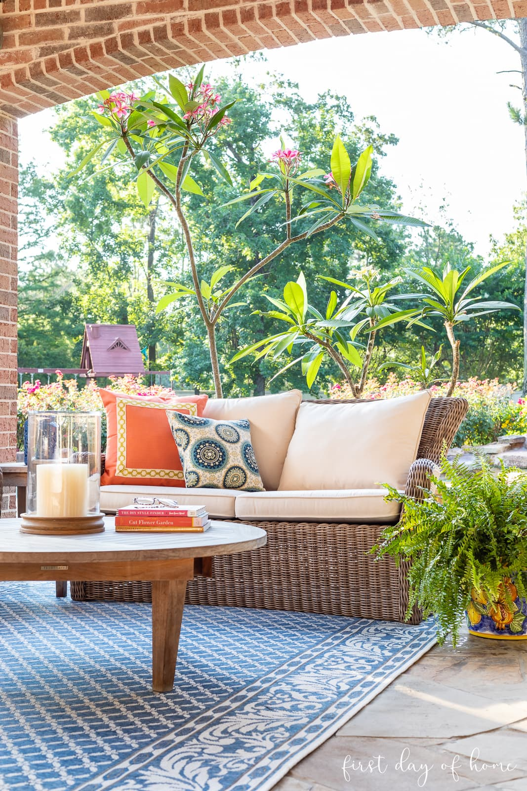 Back patio decor with settee and colorful throw pillows with area rug and potted plants