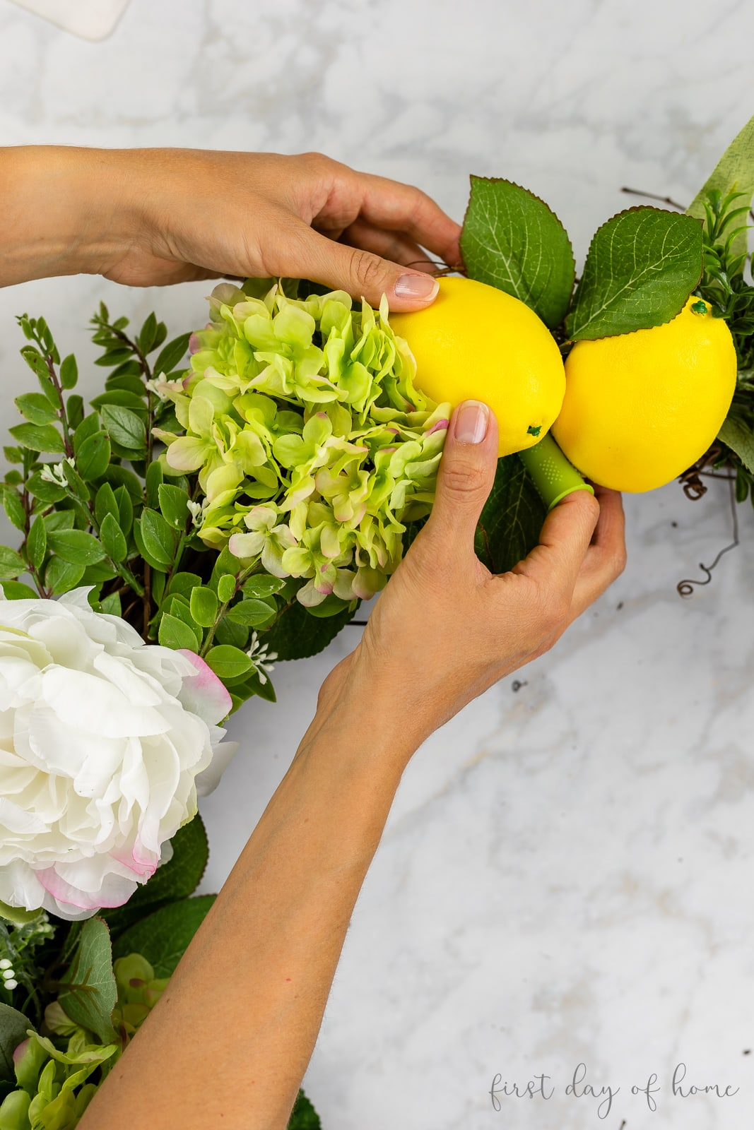Gluing faux lemons on grapevine wreath with hydrangeas