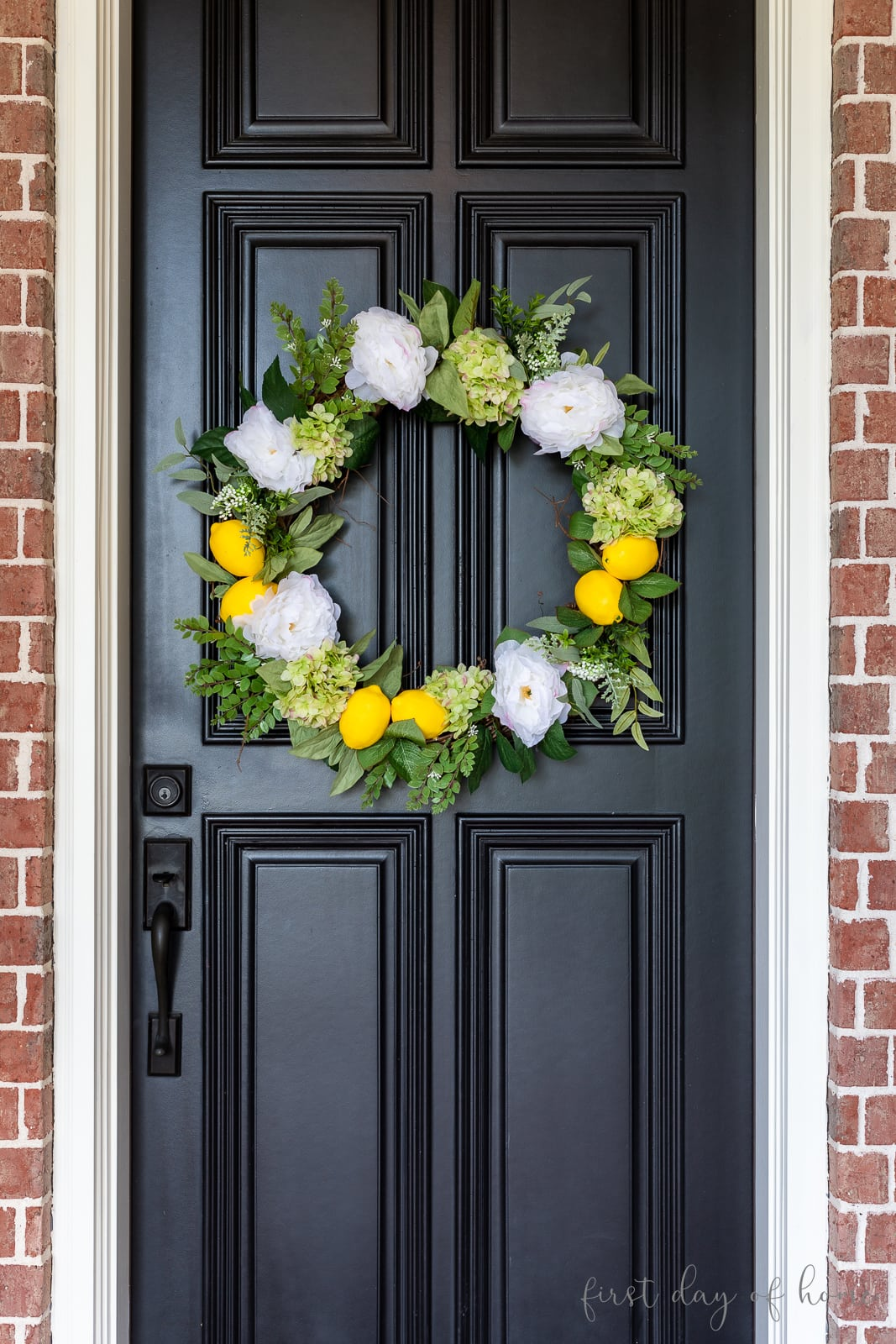 Grapevine wreath with lemons, hydrangeas, peonies and greenery on black front door