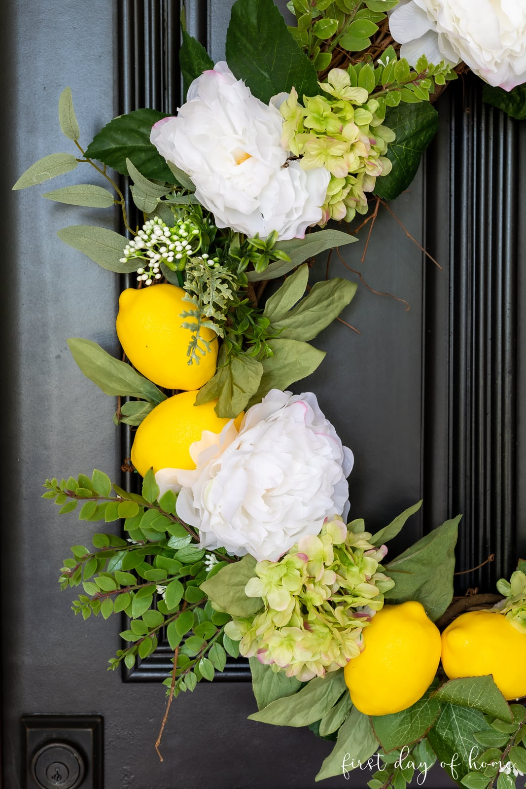Closeup of grapevine wreath with lemons, hydrangeas, and white peonies on black front door