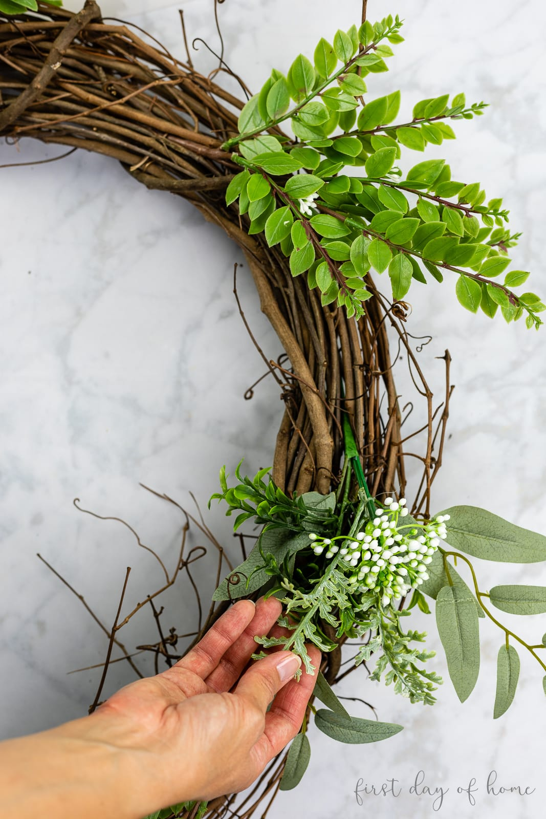 Attaching greenery picks to grapevine wreath in spiral pattern