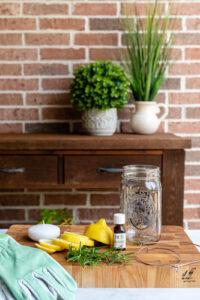 Bug repellent luminary ingredients, including lemon, rosemary, mason jar, and floating candle