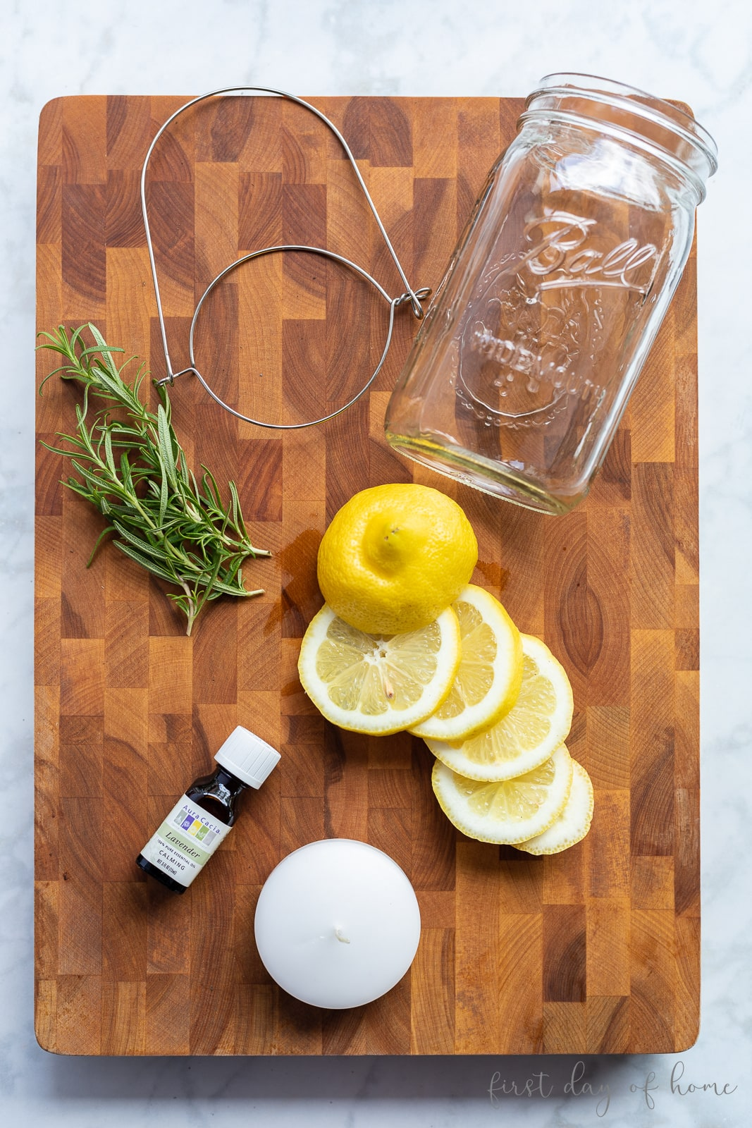 Mason jar luminary supplies, including lemon slices, rosemary, and essential oil