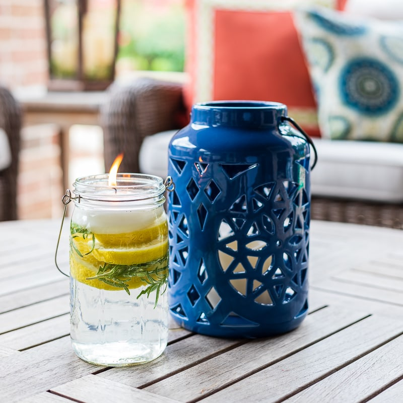 Mason jar filled with citrus, rosemary and essential oils pictured with lantern on patio table