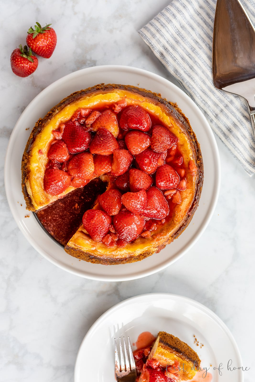 Cheesecake topped with halved strawberries in syrup with a slice cut out