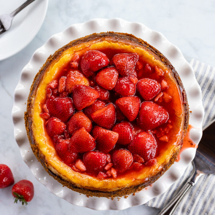 Strawberry cheesecake topped with strawberry halves in syrup