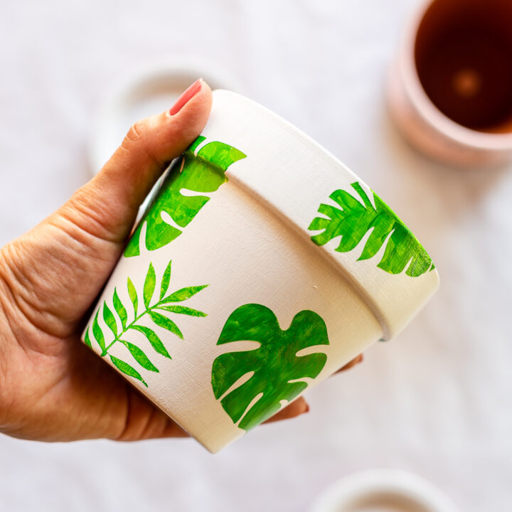 Stenciled flower pots with white base coat and green monstera leaf stencils