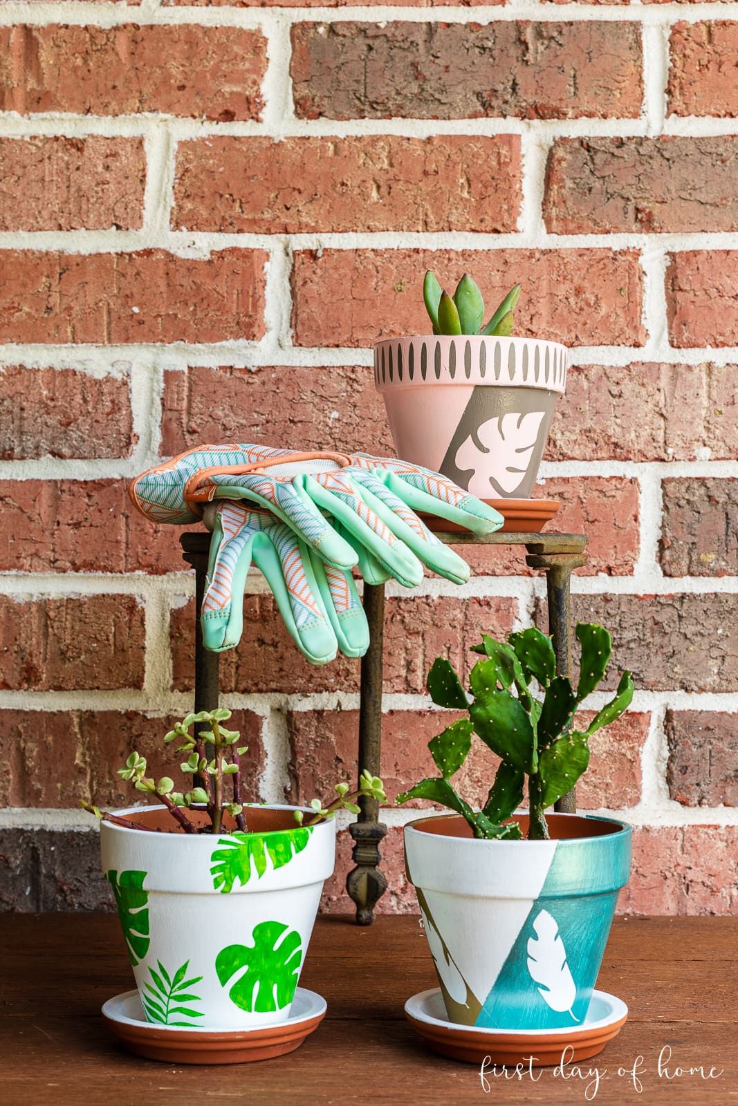 Three flower pots painted with stencil designs, pictured with gardening gloves