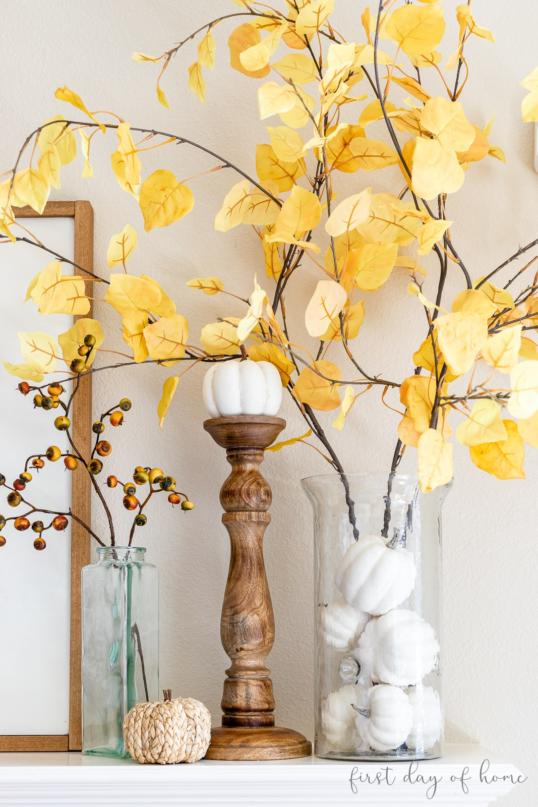 Faux aspen stems in glass hurricane jar next to pumpkin on candlestick and small glass with fall stem