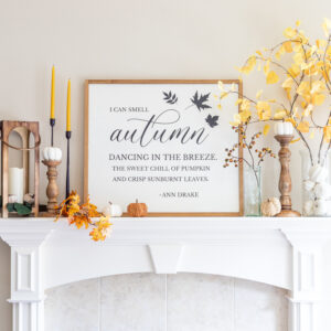Fall mantel decor with farmhouse sign, faux aspen branches, lantern, and candlesticks with pumpkins