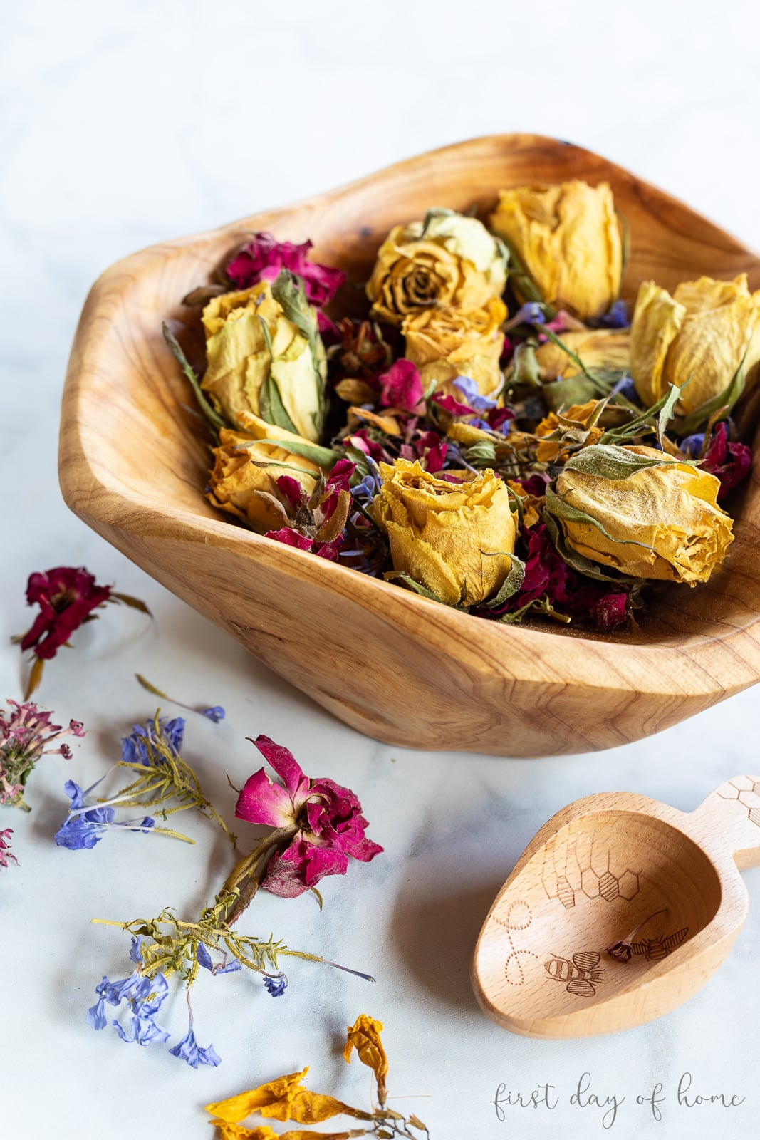 Dried flower potpourri in wooden bowl with wooden scoop