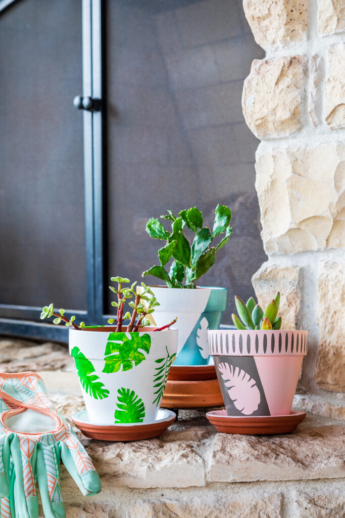 Trio of small terracotta flower pots painted with boho leaf and feather designs