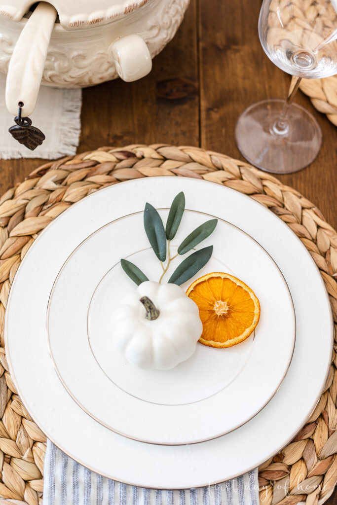 Dried orange slice with faux pumpkin and olive branch on place setting