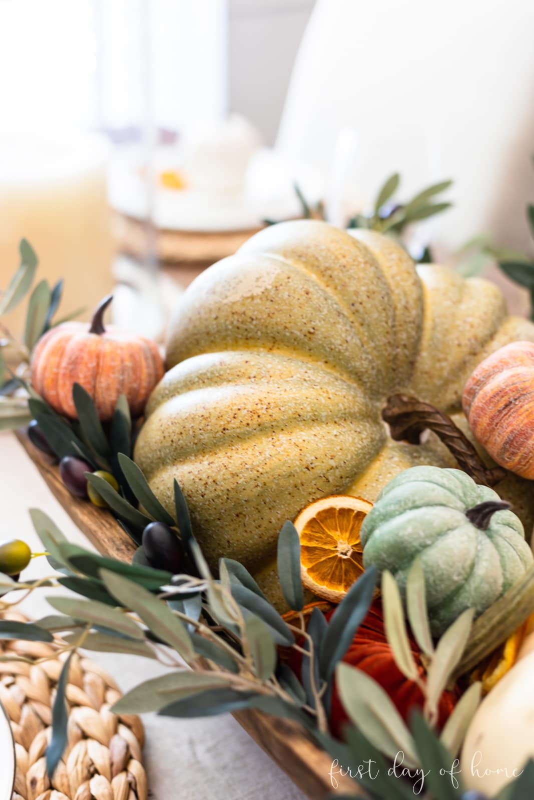 Fall centerpiece with faux pumpkins and orange slices in a dough bowl