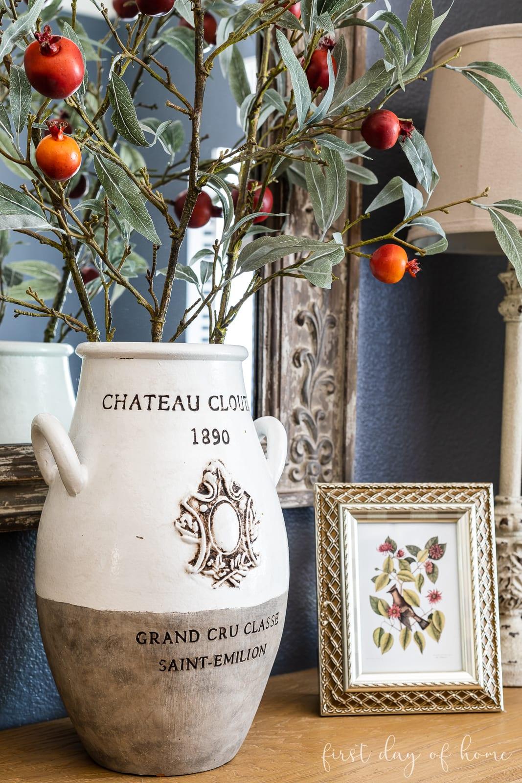 Large urn vase with fall foliage next to fall vintage botanical prints