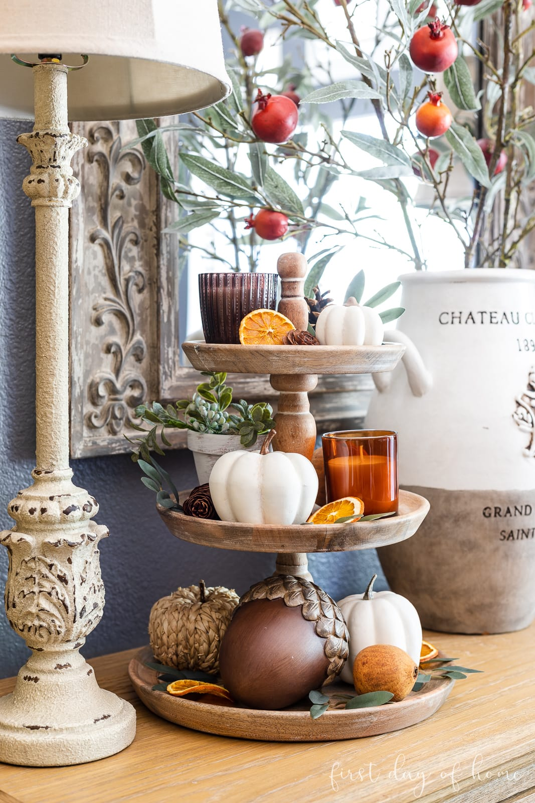 Fall tiered tray decor, including faux pumpkins, acorns, candles, and dried orange slices