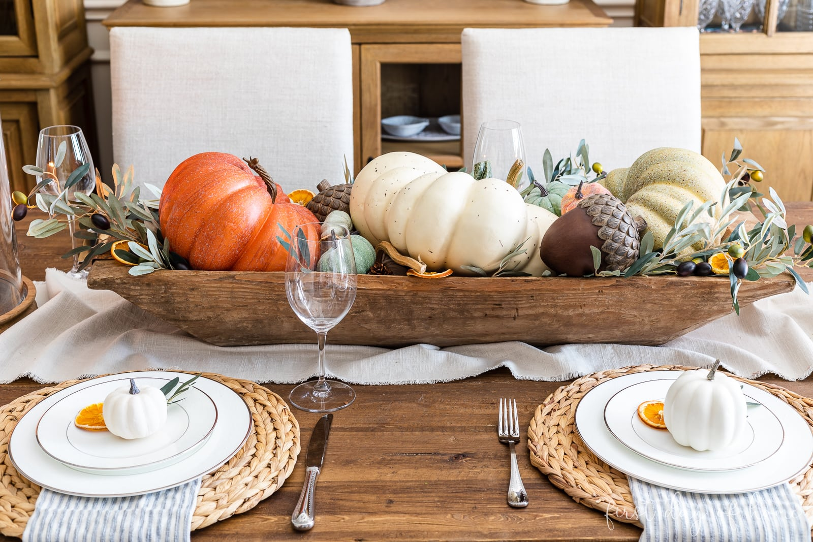 Fall table centerpiece with pumpkins, greenery and acorns