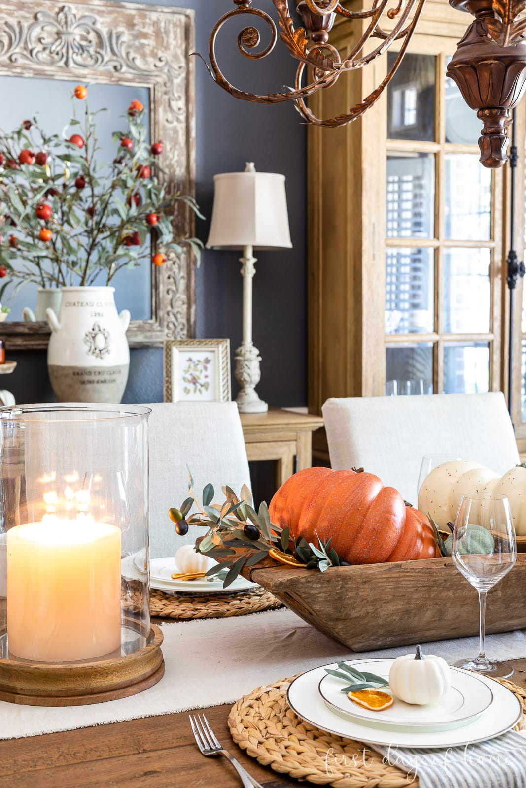 Dining table decorated for fall with dough bowl filled with pumpkins, acorns, and fall foliage