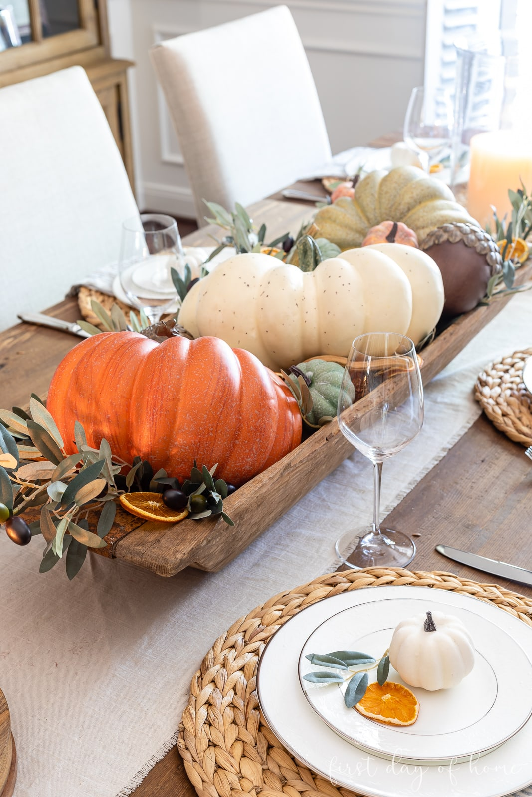 Fall table decor centerpiece with dough bowl filled with pumpkins and fall foliage
