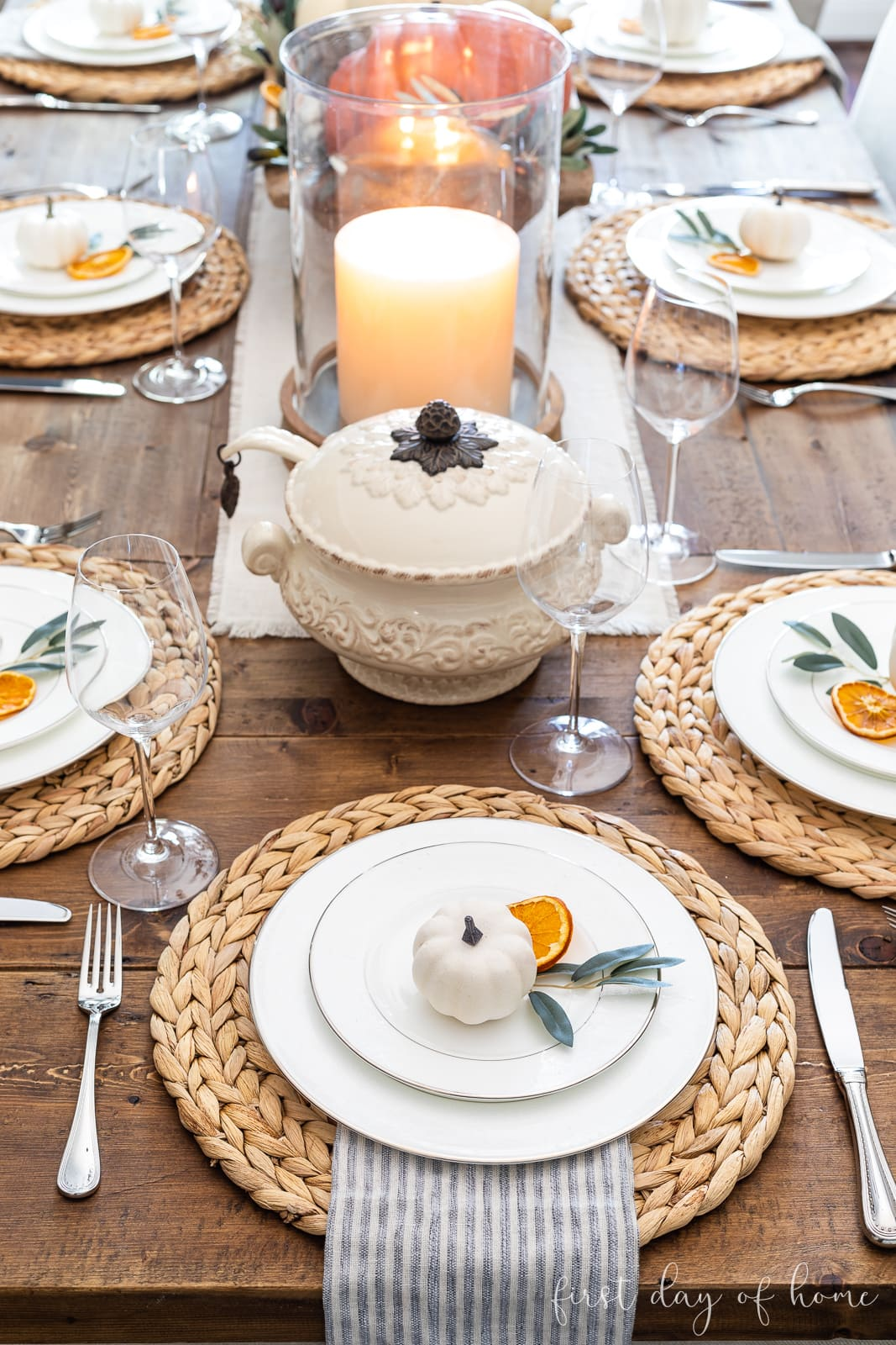 Fall place setting with woven chargers, faux pumpkins, and dried orange slices
