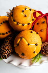 How to dry orange pomander balls (feature image of oranges with cloves inserted sitting on a white cake stand)